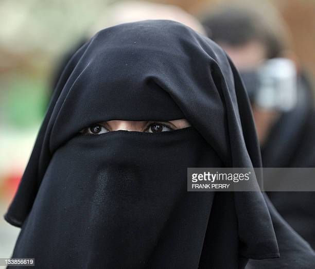 A 'wife' of French owner of a chain of butcher's and grocery shops Lies Hebbadj wearing a fullface veil looks on outside the court of justice where...