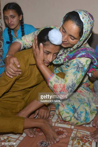 Wife of Indian army soldier Paramjeet Singh Paramjeet Kaur cries and holds her son Sahildeep Singh as she is flanked by her daughter Simrandeep Kaur...