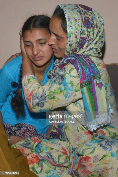 Wife of Indian army soldier Paramjeet Singh Paramjeet Kaur cries as she holds her daughter Simrandeep Kaur at their residence in Vein Pein village...