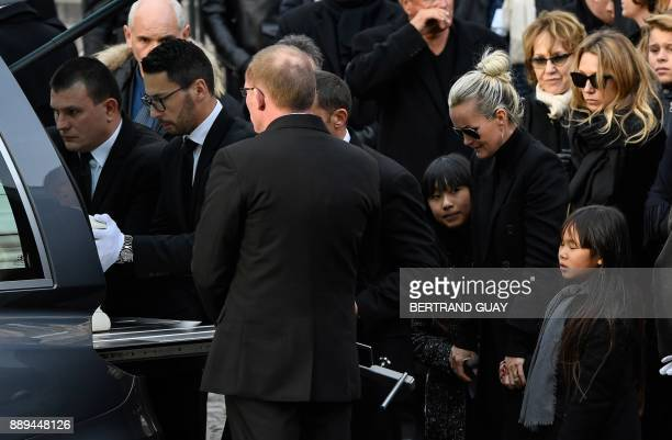 Wife of late French singer Johnny Hallyday Laeticia Hallyday and her daughters Joy and Jade Hallyday stand next to the hearse at La Madeleine Church...