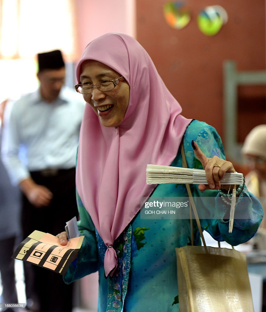 Wife of opposition leader Anwar Ibrahim, Wan Azizah (R) shows her finger marked with the idelible ink prior to casting her vote at a polling station in Permatang Pauh, Penang on May 5, 2013. Malaysians voted in their first election in history with a change of government at stake, as a decades-old regime battles to hold off a rising opposition pledging sweeping reform..