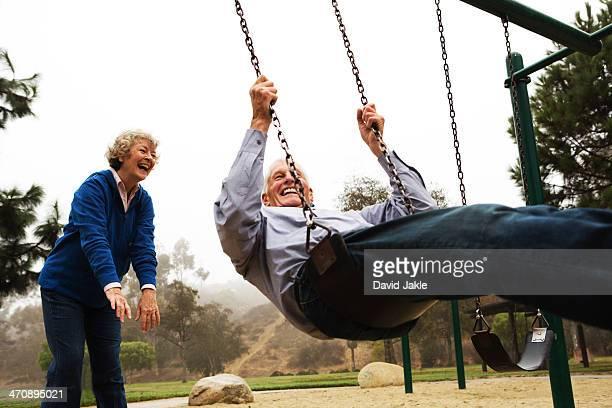 Wife pushing husband on swing