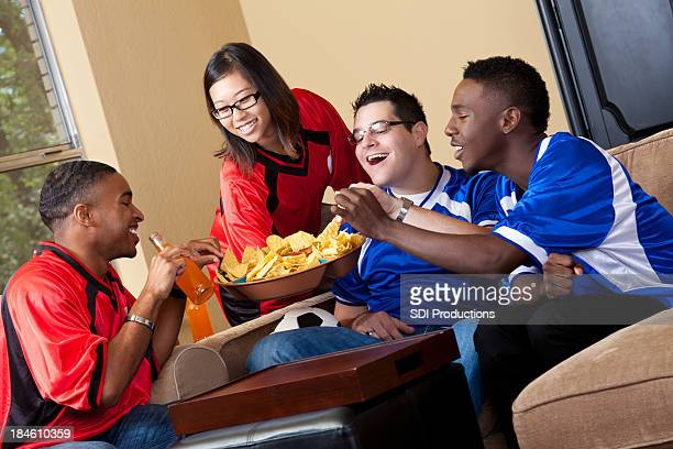 Wife serving chips to husband and friends during soccer game