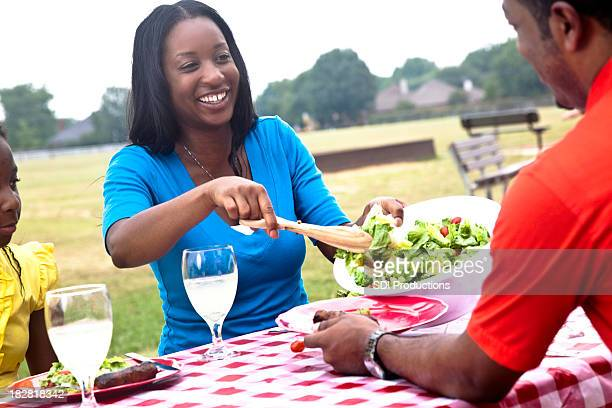 Wife Serving Salad at Outdoor Picnic