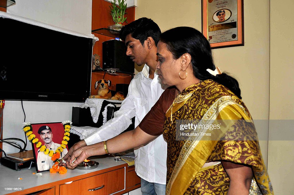 Wife Snehalata and son Devesh of 26/11 Martyr, Head Constable Murlidhar Choudhary lights a lamp in front of his picture to celebrate the news of Ajmal Kasab's hanging on November 21, 2012 in Mumbai, India. Terrorist Ajmal Kasab sentenced to death for his role in November 26, 2008 terror attack on Mumbai was hanged to death at Yerwada Jail on November 21, 2012 in Pune, India.