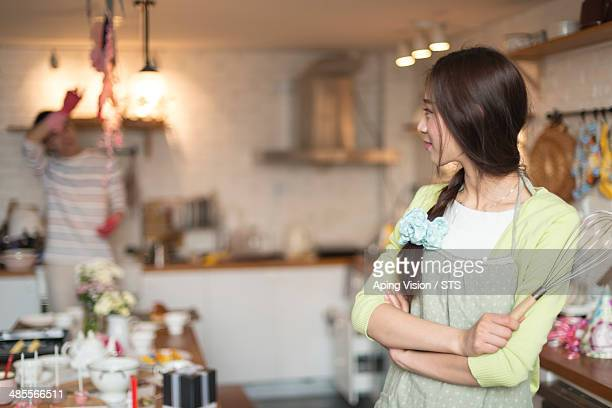 wife standing while husband washing dishes