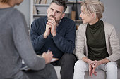 Wife supporting her husband in therapy with the man listening curious to counsellor in gray office
