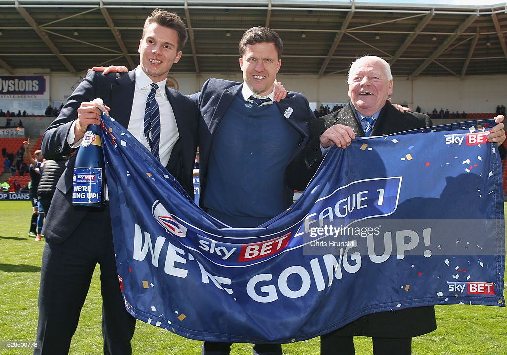Wigan Athletic chairman David Sharpe, manager Gary Caldwell and owner Dave Whelan celebrate promotion to the Championship after the Sky Bet League One match between Blackpool and Wigan Athletic at Bloomfield Road on April 30, 2016 in Blackpool, England.
