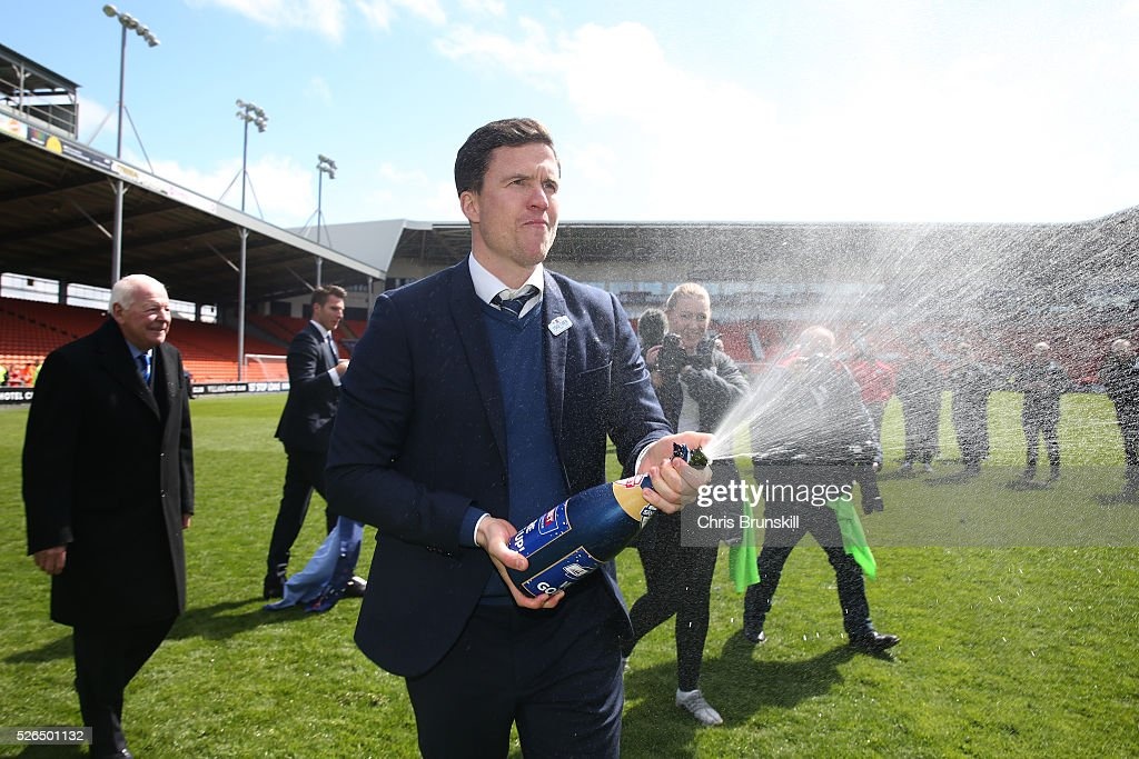 Wigan Athletic manager Gary Caldwell sprays champagne as they celebrate promotion to the Championship after the Sky Bet League One match between Blackpool and Wigan Athletic at Bloomfield Road on April 30, 2016 in Blackpool, England.