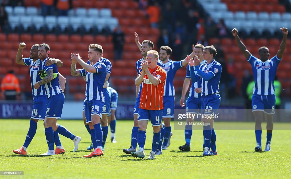 Wigan Athletic players celebrate promotion to the Championship after the Sky Bet League One match between Blackpool and Wigan Athletic at Bloomfield Road on April 30, 2016 in Blackpool, England.