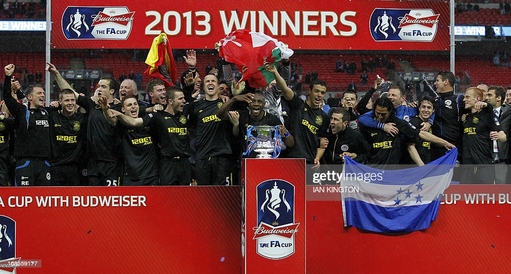 Wigan Athletic players celerbate with the FA Cup after winning the English FA Cup final football match between Manchester City and Wigan Athletic at Wembley Stadium in London on May 11, 2013.