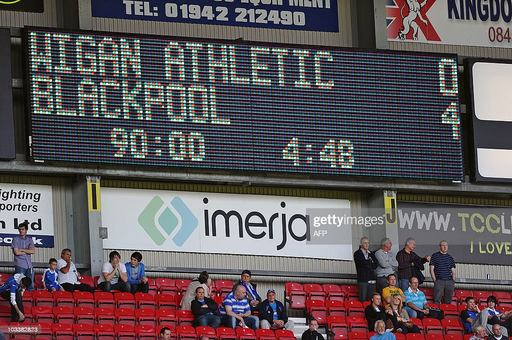 Wigan Athletic supporters sit below the scoreboard after they lose 04 to Blackpool in the English Premier League football match between Wigan...