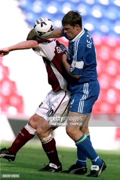 Wigan Athletic's Arjan De Zeeuw challenges Northampton Town's Marco Gabbiadini