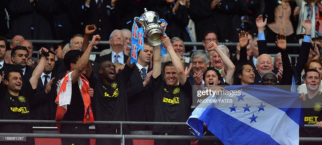 Wigan Athletic's Barbadian defender Emmerson Boyce (CL) and Wigan Athletic's Scottish defender Gary Caldwell (CR) raise the FA Cup after winning the English FA Cup final football match between Manchester City and Wigan Athletic at Wembley Stadium in London on May 11, 2013. Substitute Ben Watson scored an injury-time winner to give Wigan Athletic a sensational 1-0 win over Manchester City at Wembley Stadium on Saturday in the biggest FA Cup final upset in 25 years.