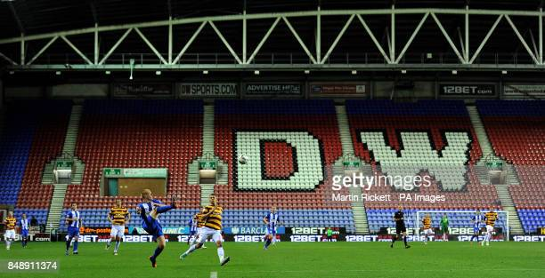 Wigan Athletic's Ben Watson clears the ball from Bradford City's Nahki Wells in front of an empty stand during the Capital One Cup Fourth Round match...