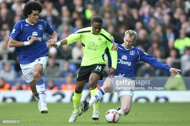 Wigan Athletic's Charles N'Zogbia and Everton's Tony Hibbert battle for the ball as Everton's Marouane Fellaini looks on