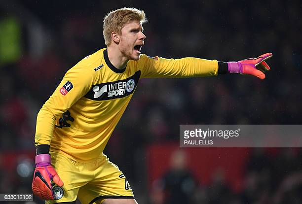 Wigan Athletic's Danish goalkeeper Jakob Haugaard shouts during the English FA Cup fourth round football match between Manchester United and Wigan...