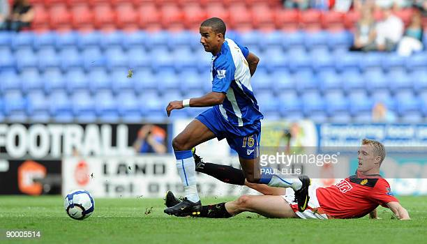Wigan Athletic's English forward Scott Sinclair is challenged by Manchester United's Scottish midfielder Darren Fletcher during the English Premier...