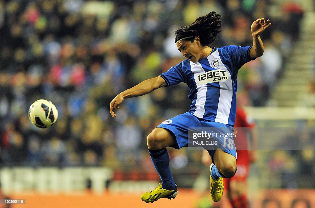 Wigan Athletic's Honduran midfielder Roger Espinoza jumps for the ball during the English Premier League football match between Wigan Athletic and Liverpool at The DW Stadium in Wigan, northwest England, on March 2, 2013. USE. No use with unauthorized audio, video, data, fixture lists, club/league logos or 'live' services. Online in-match use limited to 45 images, no video emulation. No use in betting, games or single club/league/player publications.