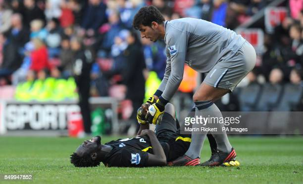 Wigan Athletic's Joel Robles tries to pickup injured Norwich City striker Kei Kamara during the Barclays Premier League match at the DW Stadium Wigan