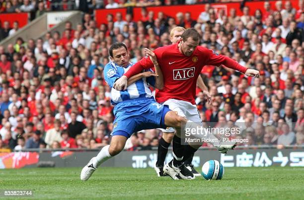 Wigan Athletic's Josip Skoko challenges Manchester United's Wayne Rooney for the ball