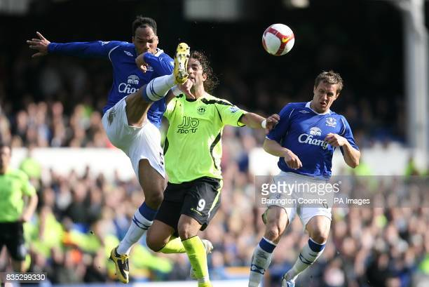 Wigan Athletic's Mido and Everton's Joleon Lescott battle for the ball as Everton's Phil Jagielka avoids the challenge