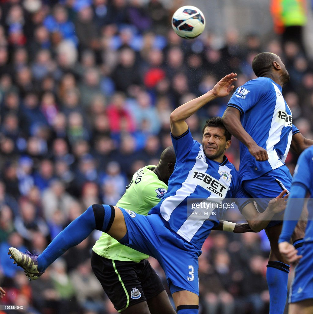 "Wigan Athletic's Paraguayan defender Antolin Alcaraz (C) jumps for the ball during the English Premier League football match between Wigan Athletic and Newcastle United at The DW Stadium in Wigan, north-west England, on March 17, 2013. USE. No use with unauthorized audio, video, data, fixture lists, club/league logos or ""live"" services. Online in-match use limited to 45 images, no video emulation. No use in betting, games or single club/league/player publications"