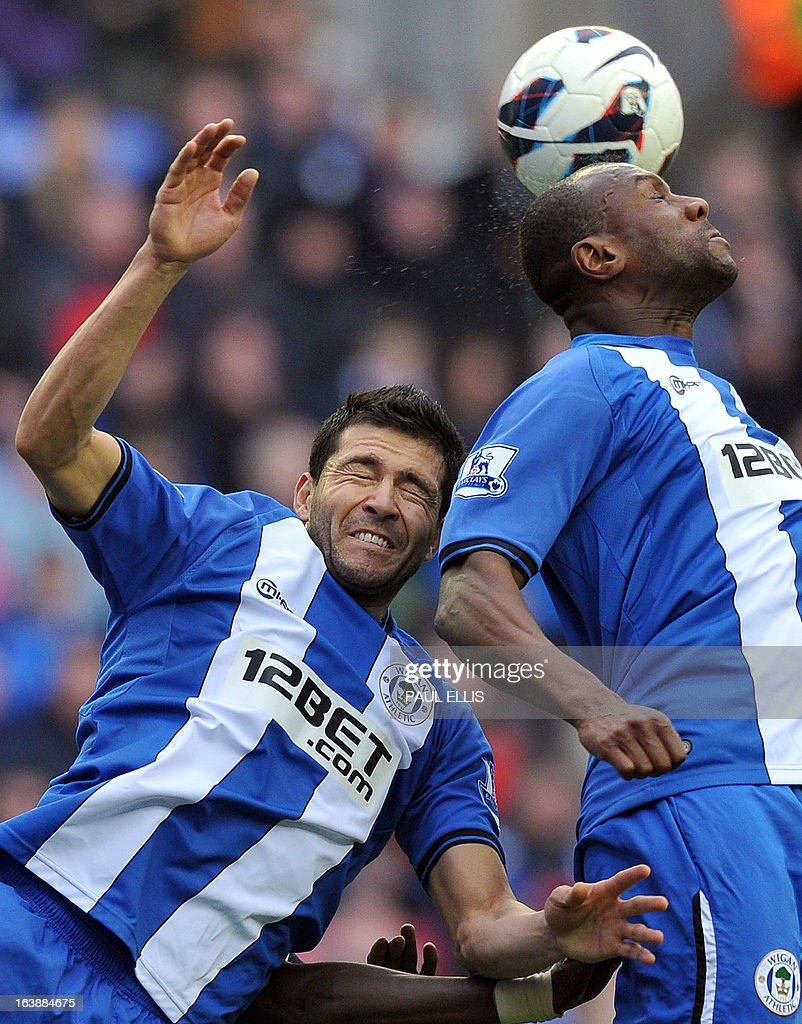 "Wigan Athletic's Paraguayan defender Antolin Alcaraz (L) jumps for the ball with Wigan Athletic's Barbadian defender Emmerson Boyce during the English Premier League football match between Wigan Athletic and Newcastle United at The DW Stadium in Wigan, north-west England, on March 17, 2013. USE. No use with unauthorized audio, video, data, fixture lists, club/league logos or ""live"" services. Online in-match use limited to 45 images, no video emulation. No use in betting, games or single club/league/player publications"