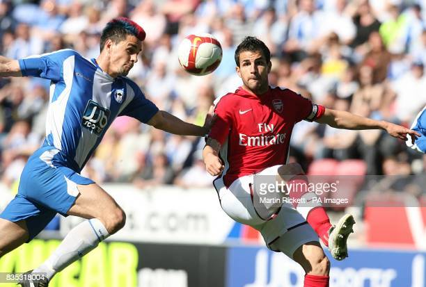 Wigan Athletic's Paul Scharner and Arsenal's Cesc Fabregas battle for the ball