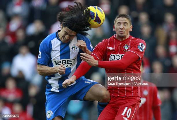 Wigan Athletic's Roger Espinoza jumps with Southampton's Gastoacuten Ramiacuterez during the Barclays Premier League match at the DW Stadium Wigan