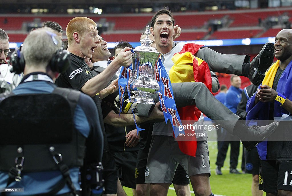 Wigan Athletic's Spanish manager Roberto Martinez (C) is held aloft by his players as goal scorer Wigan Athletic's English midfielder Ben Watson (L) and Wigan Athletic's Spanish goalkeeper Joel Robles (2R) hold the FA Cup after winning the English FA Cup final football match between Manchester City and Wigan Athletic at Wembley Stadium in London on May 11, 2013. Substitute Ben Watson scored an injury-time winner to give Wigan Athletic a sensational 1-0 win over Manchester City at Wembley Stadium on Saturday in the biggest FA Cup final upset in 25 years.