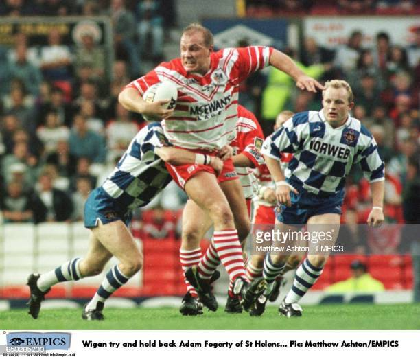 Wigan try and hold back Adam Fogerty of St Helens
