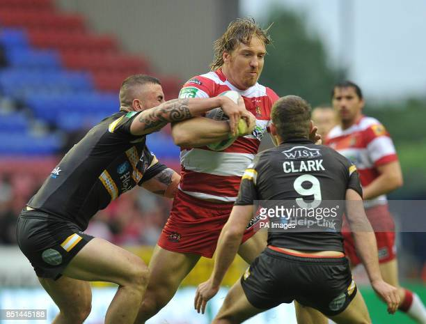 Wigan Warriors' Andy Powell is tackled by Castleford Tigers' Daryl Clark and Jonathan Walker during the Super League match at the DW Stadium Wigan