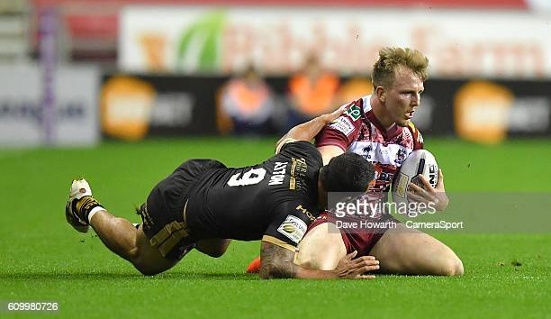 Wigan Warriors' Dan Sarginson is tackled by Catalans Dragons' Paul Aiton during the First Utility Super League Super 8s Round 7 match between Wigan...