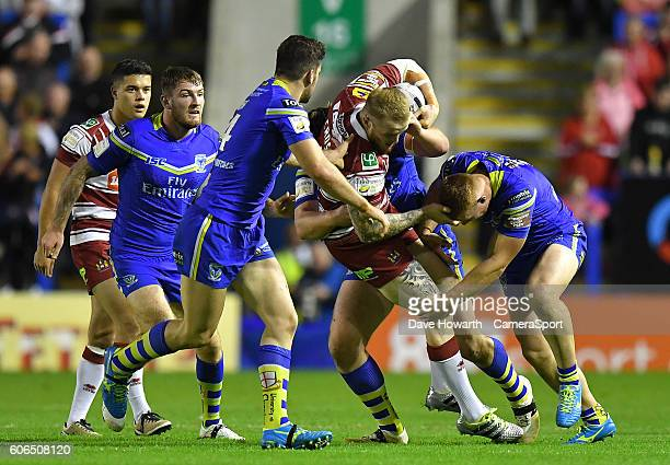 Wigan Warriors' Dom Crosby is tackled by Warrington Wolves' Jack Hughes and Chris Hill during the First Utility Super League Super 8s Round 6 match...