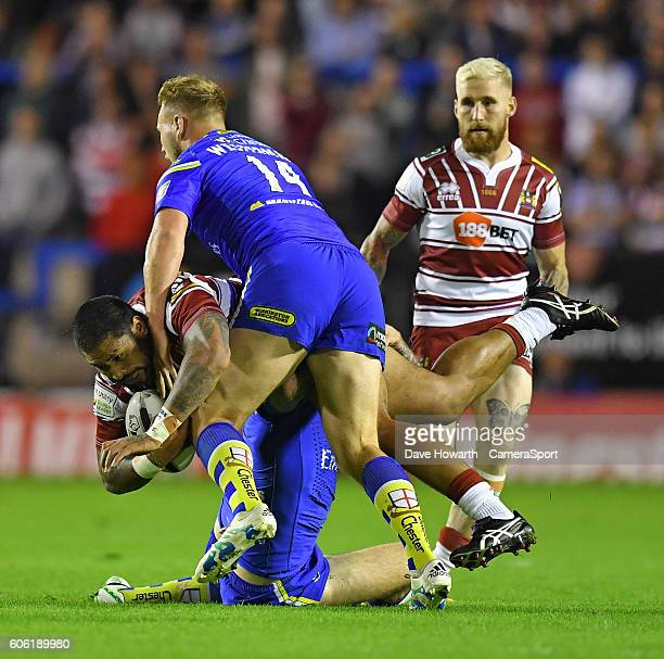 Wigan Warriors' FrankPaul Nu'uausala is tackled by Warrington Wolves' Joe Westerman and Daryl Clark during the First Utility Super League Super 8s...