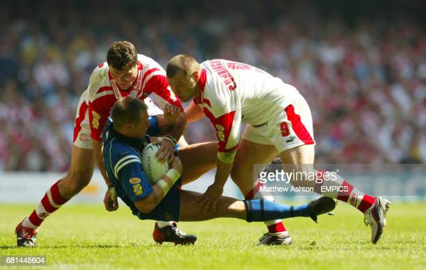 Wigan Warriors' Gareth Hock is tackled by St Helens' Jason Hooper and Keiron Cunningham