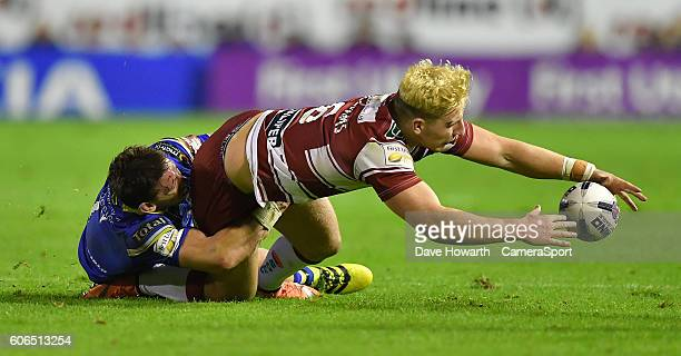 Wigan Warriors' George Williams is tackled by Warrington Wolves' Kurt Gidley during the First Utility Super League Super 8s Round 6 match between...