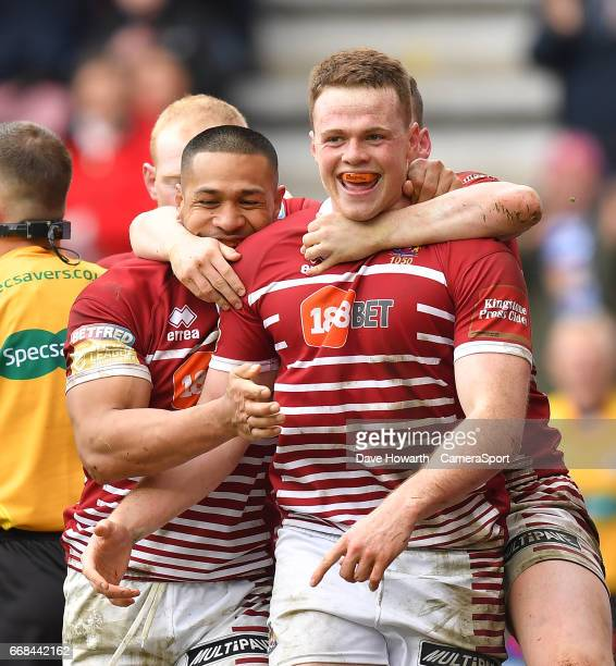 Wigan Warriors' Joe Burgess is congratulated on scoring his team's 5th try during the Betfred Super League Round 9 match between Wigan Warriors and...