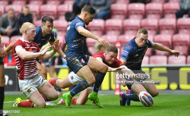 Wigan Warriors' Joe Burgess scores his team's opening try during the Betfred Super League Round 9 match between Wigan Warriors and St Helens at DW...