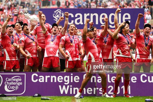 Wigan Warriors players celebrate with the Carnegie Cup after victory over Leeds Rhinos following the Carnegie Challenge Cup Final between Leeds...