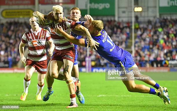 Wigan Warriors' Sam Tomkins runs in to score his sides 2nd try despite the attentions of Warrington Wolves' Joe Westerman during the First Utility...