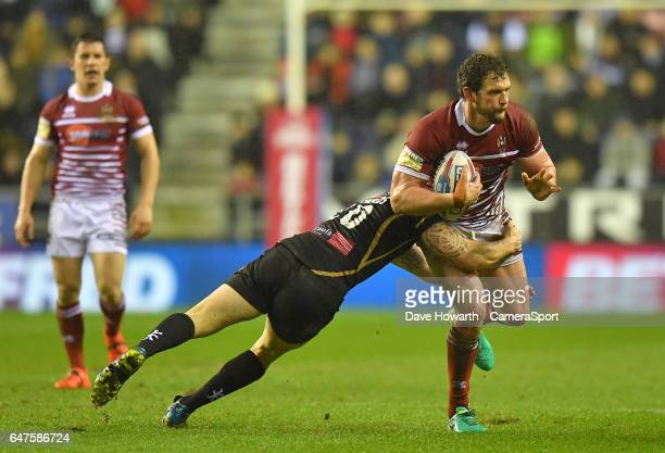 Wigan Warriors' Sean O'Loughlin is tackled during the Betfred Super League Round 3 match between Wigan Warriors and Leigh Centurions at DW Stadium on...