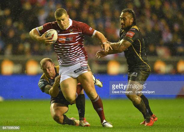 Wigan Warriors' Tony Clubb is tackled during the Betfred Super League Round 3 match between Wigan Warriors and Leigh Centurions at DW Stadium on...