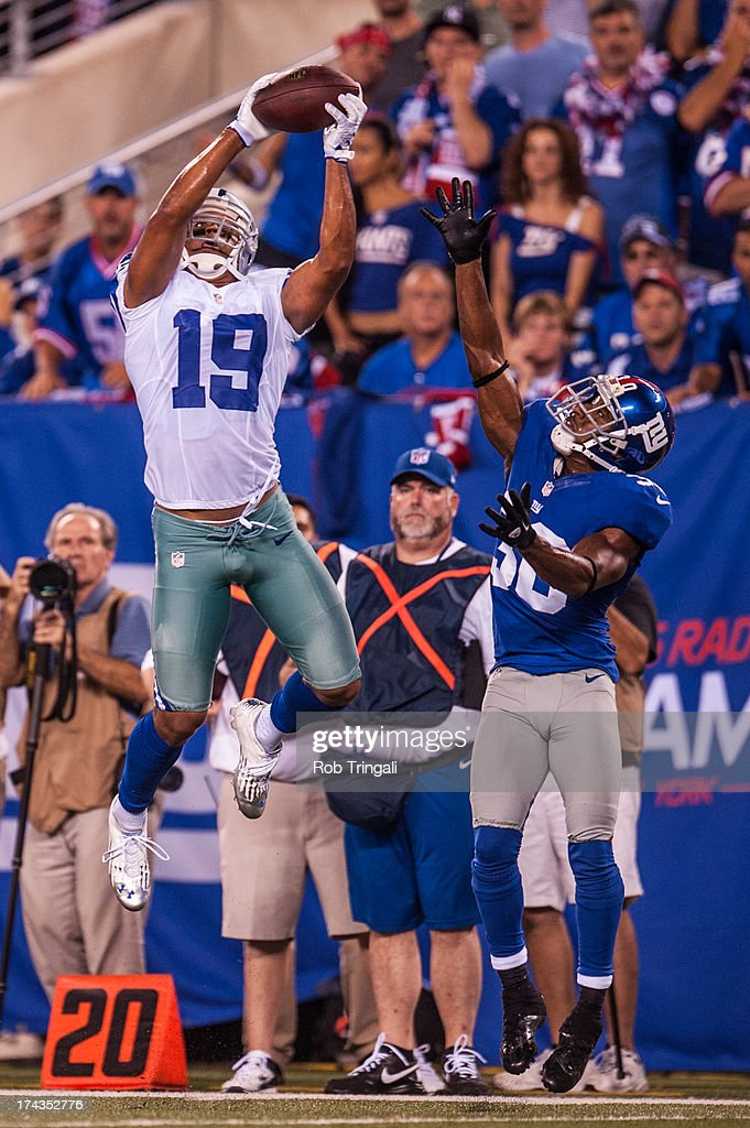 Wiide receiver Miles Austin of the Dallas Cowboys makes a leaping catch over defensive back Justin Tryon of the New York Giants during the game at...
