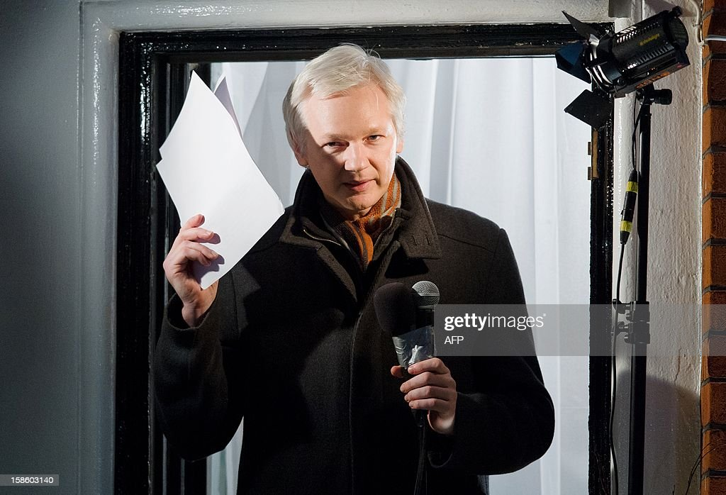 Wikileaks founder Julian Assange addresses members of the media and supporters from the window of the Ecuadorian embassy in Knightsbridge, west London on December 20, 2012. WikiLeaks will release one million documents next year affecting every country in the world, founder Julian Assange said in a speech from the balcony of the Ecuadorian embassy in London. In a 'Christmas message' marking six months since he sought asylum in the embassy to avoid extradition to Sweden over claims of rape and sexual assault, Assange also said the door was open to negotiations. AFP PHOTO/Leon Neal