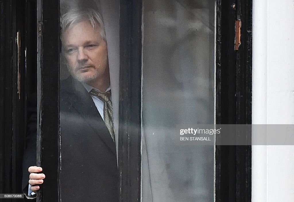 TOPSHOT - WikiLeaks founder Julian Assange comes out on the balcony of the Ecuadorian embassy to address the media in central London on February 5, 2016. During a press conference on February 5 Julian Assange, speaking via video-link, called for Britain and Sweden to 'implement' a UN panel finding saying that he should be able to walk free from Ecuador's embassy, where he has lived in self-imposed confinement since 2012. / AFP / BEN