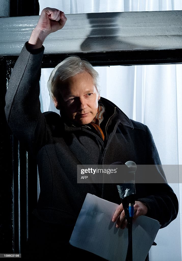 Wikileaks founder Julian Assange gestures as he addresses members of the media and supporters from the window of the Ecuadorian embassy in Knightsbridge, west London on December 20, 2012. WikiLeaks will release one million documents next year affecting every country in the world, founder Julian Assange said in a speech from the balcony of the Ecuadorian embassy in London. In a 'Christmas message' marking six months since he sought asylum in the embassy to avoid extradition to Sweden over claims of rape and sexual assault, Assange also said the door was open to negotiations. AFP PHOTO/Leon Neal
