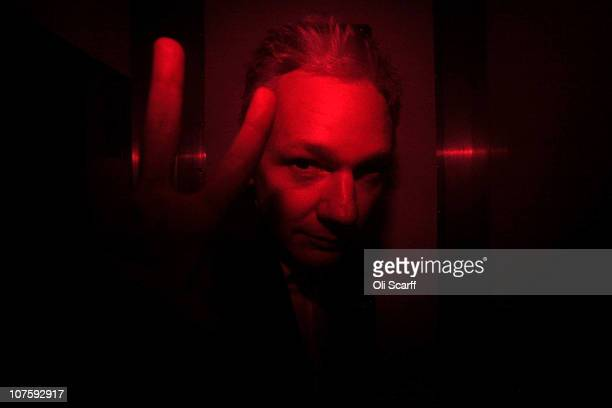 Wikileaks founder Julian Assange gestures inside a prison van with red windows as he leaves Westminster Magistrates Court on December 14 2010 in...