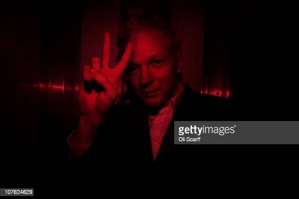 Wikileaks founder Julian Assange gestures inside a prison van with red windows as he arrives at the Royal Courts of Justice on December 16 2010 in...